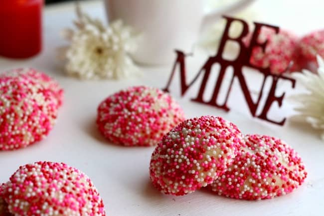 Sprinkle sugar cookies with a Be Mine sign and white flowers.