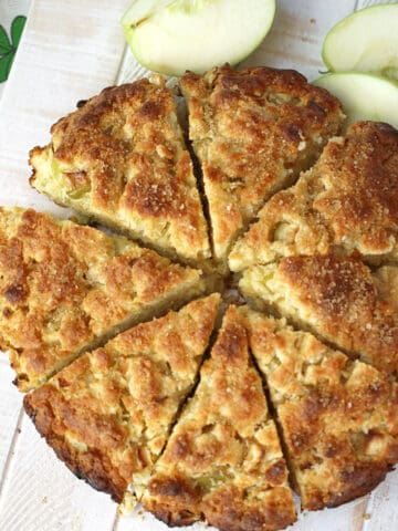 Irish Apple Scones cut into wedges on a white cutting board.