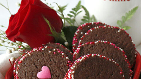 A heart shaped bowl filled with chocolate cookies.