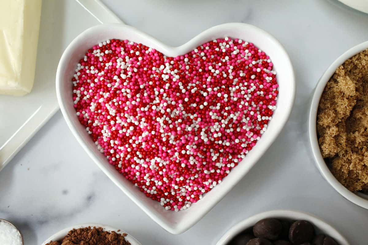 red, white and pink nonpareil sprinkles in a heart bowl