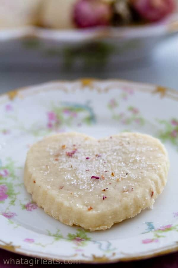 A heart shaped Rose Scented Shortbread cookie on a floral plate.