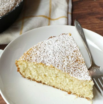 A slice of vanilla bean cake topped with powdered sugar.