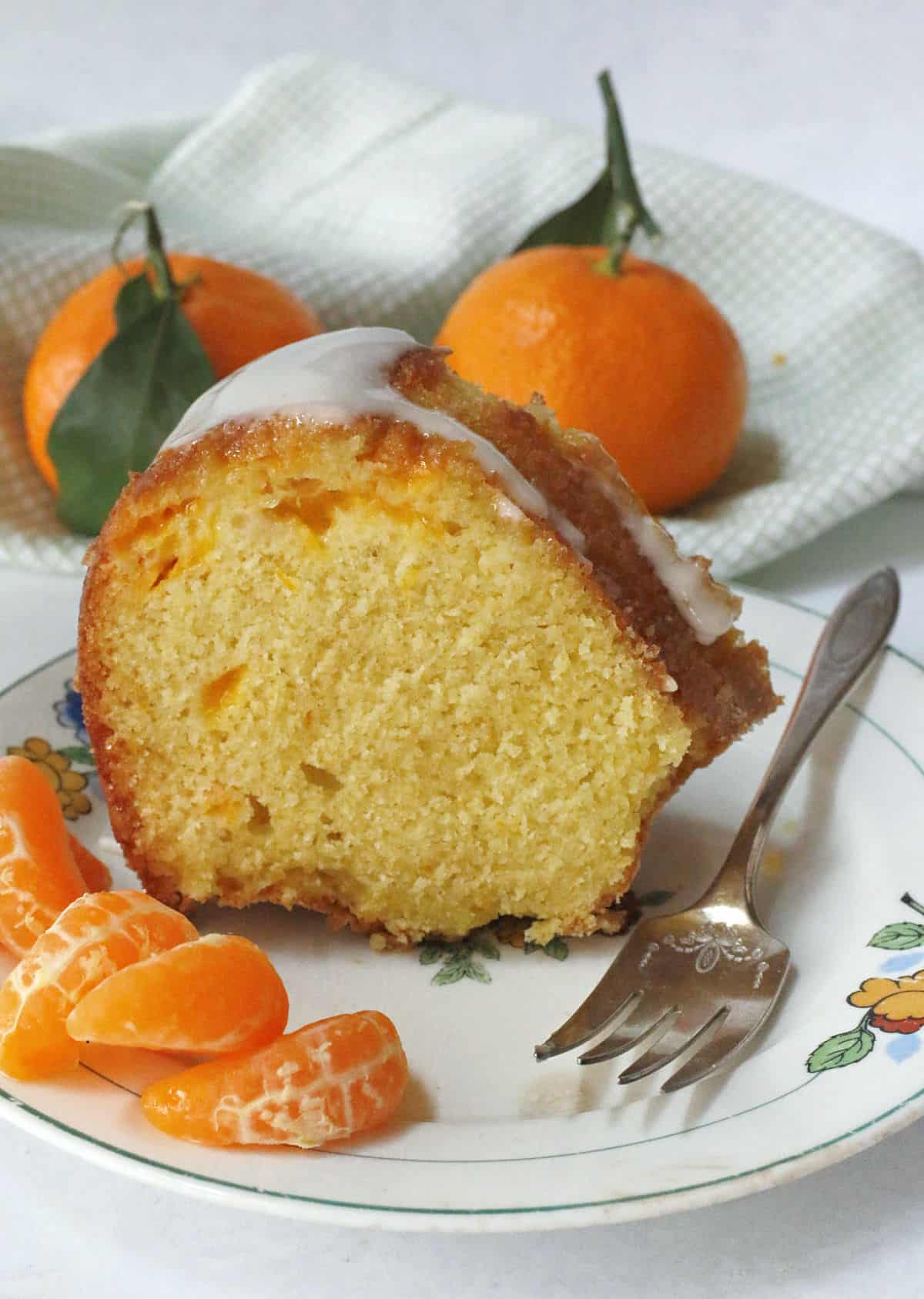 A slice of orange cake on a white plate with a fork and whole oranges.