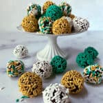 Dark chocolate truffles with sprinkles on a cake stand.