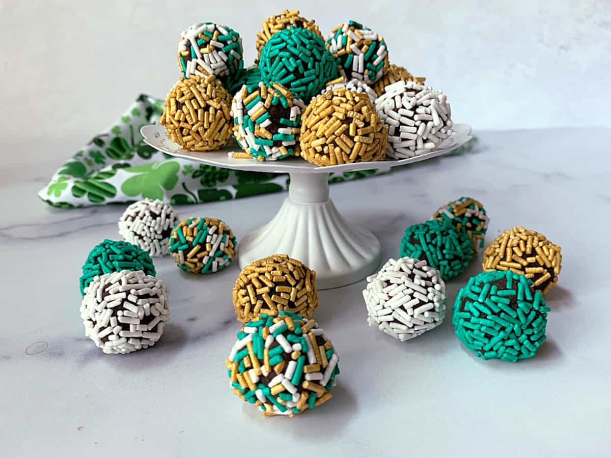 Irish cream truffles with sprinkles on a cake stand.