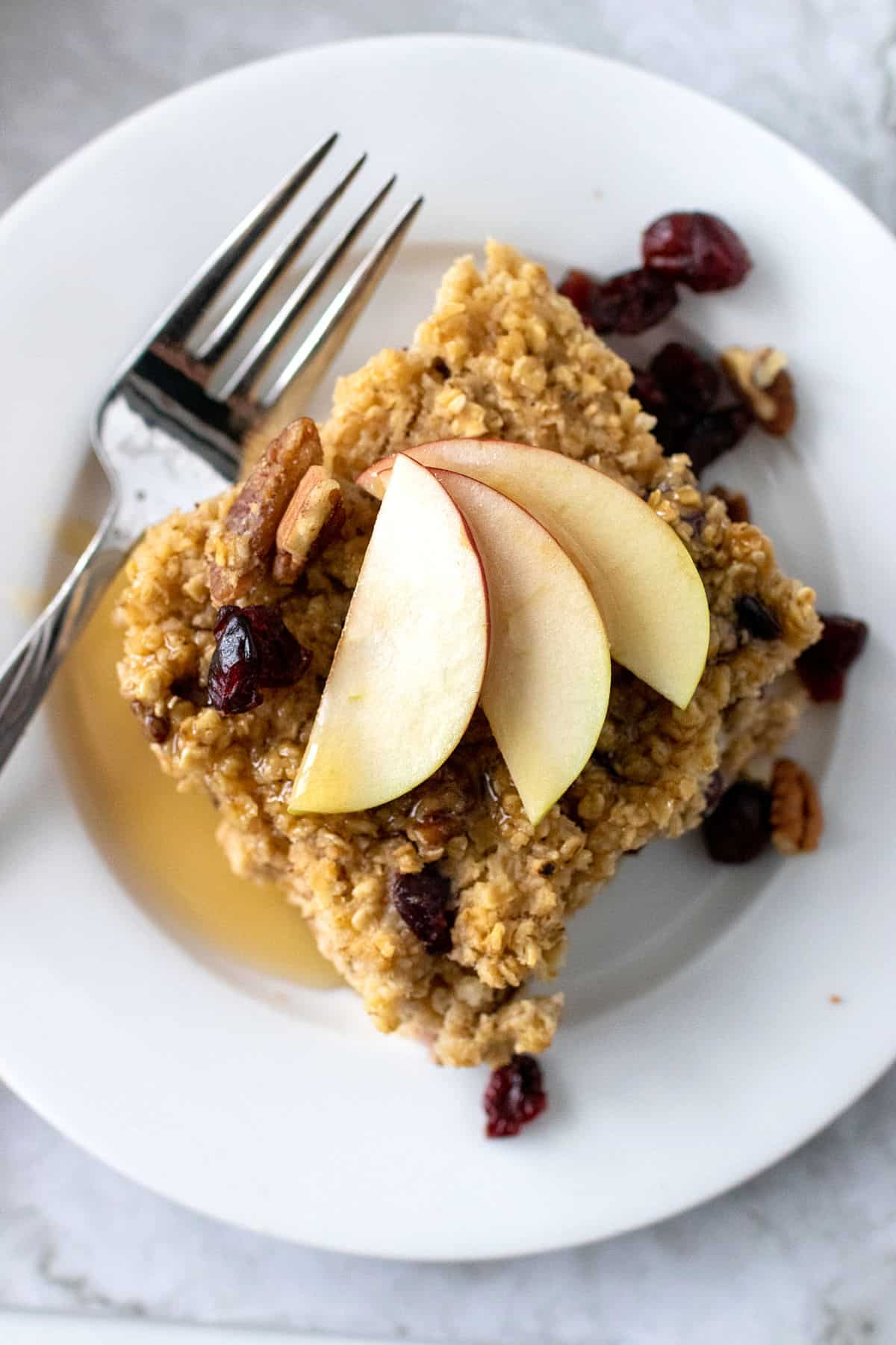 A white plate with a slice of baked oatmeal with pecans, cranberries and apples.