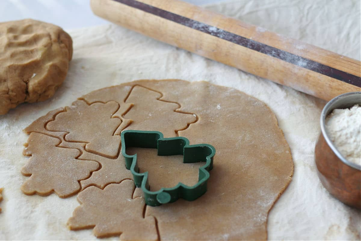 Cutting out Christmas tree spice cookies on a floured surface with a rolling pin.