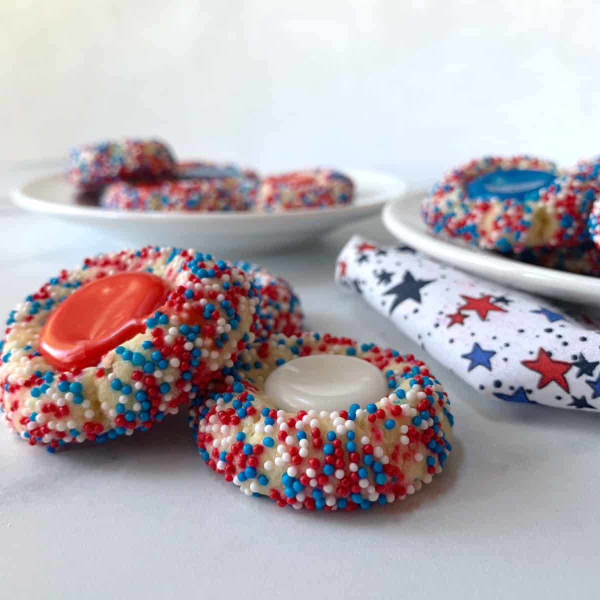 Red, white and blue thumbprint cookies on white plates.