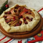 Apple cranberry galette on a brown board.
