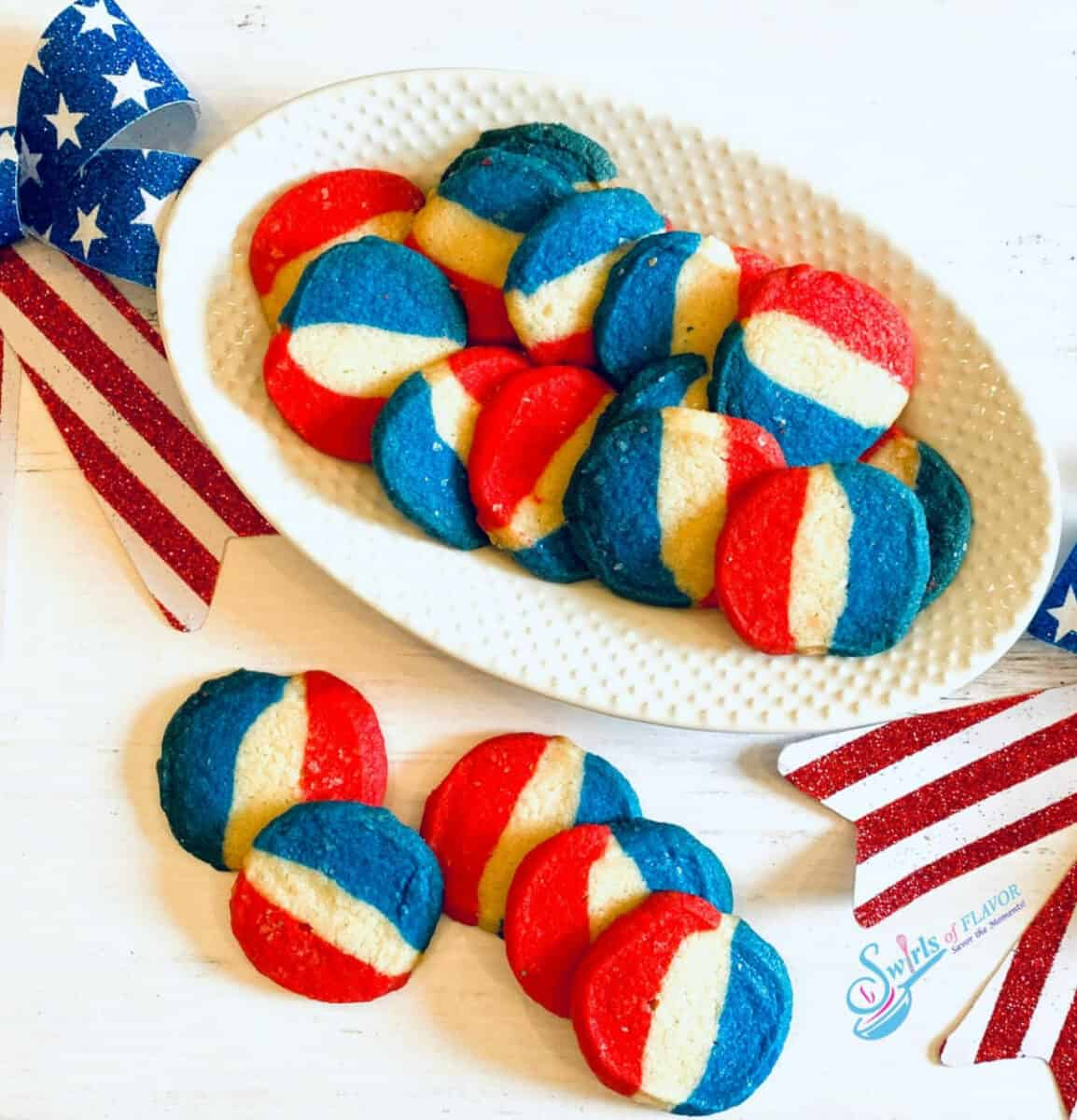 Red, white and blue striped sugar cookies on a white plate.