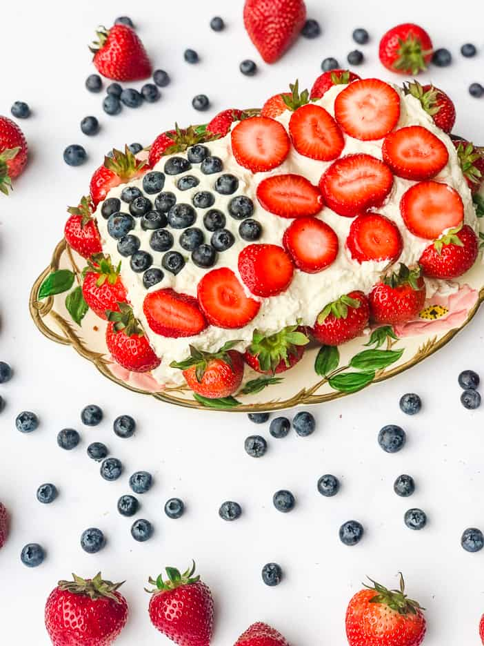 A cake made to look like the American flag with blueberries and strawberries.