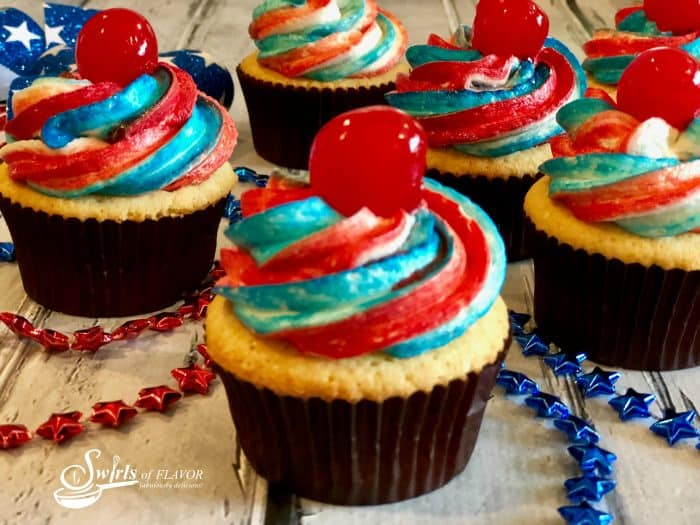 Vanilla cupcakes with red, white and blue frosting and a cherry on top.