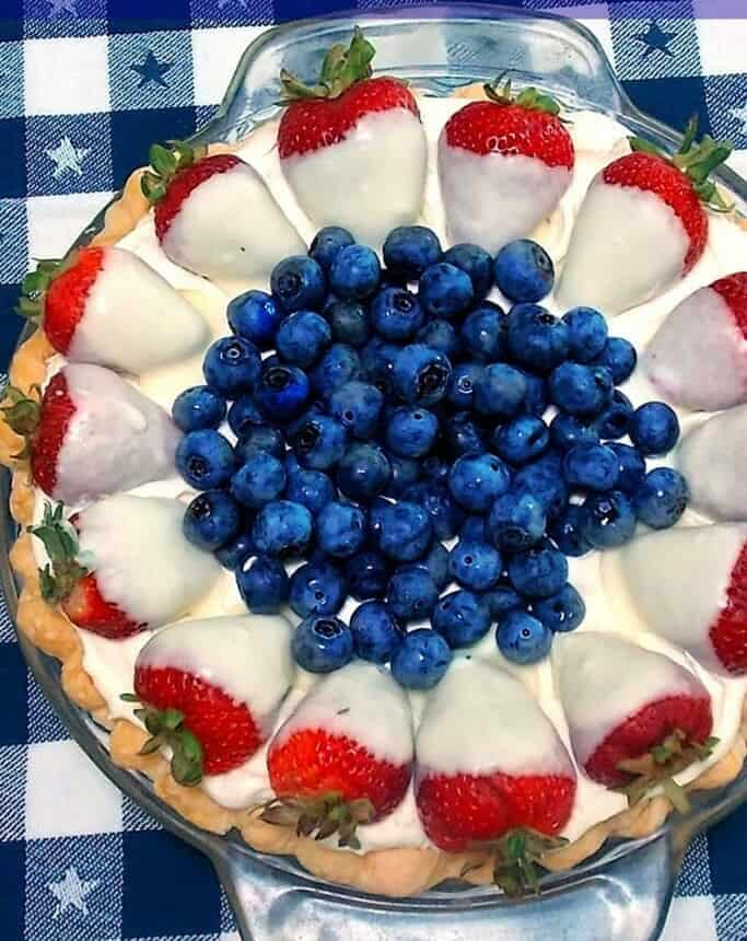 Strawberries covered in white chocoalte with blueberries in the middle of a pie plate..