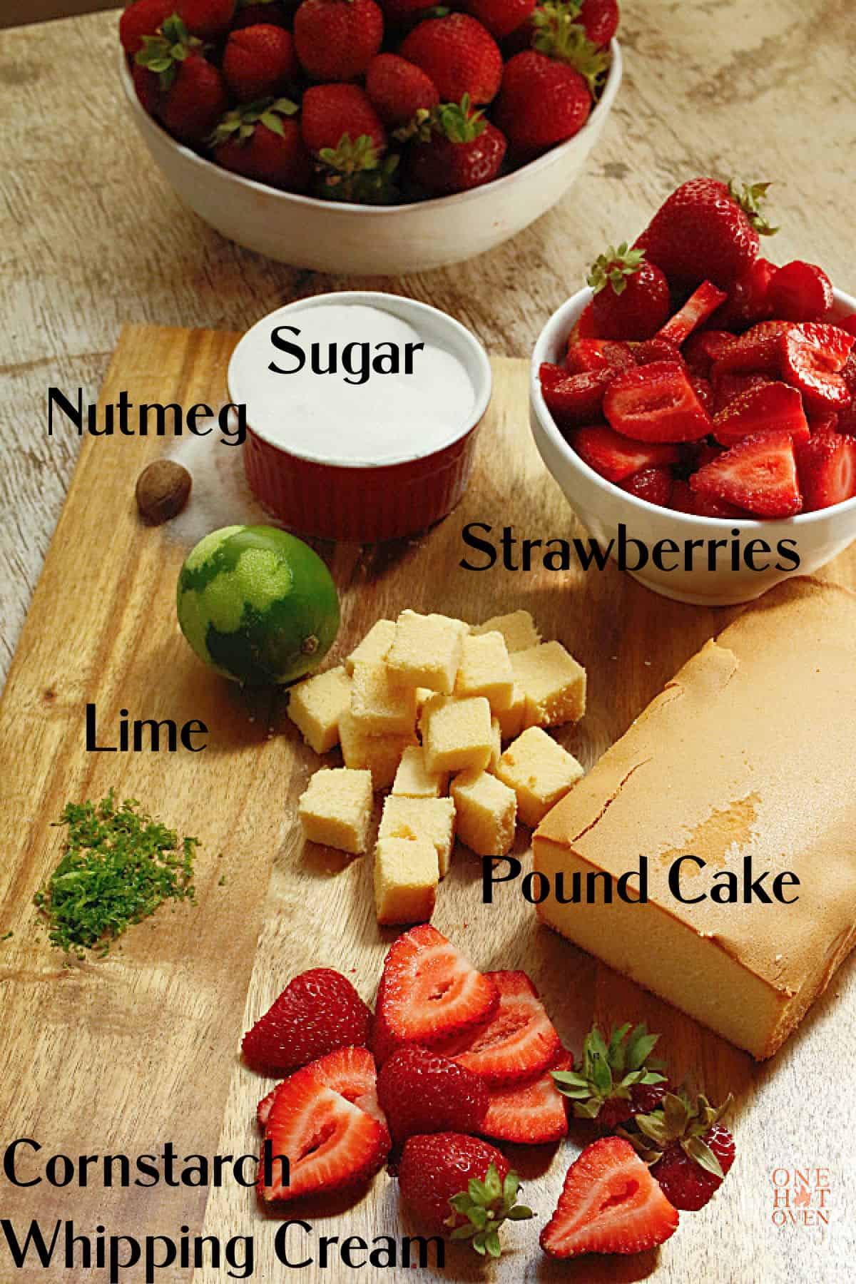 Strawberries, pound cake, lime and sugar on a brown cutting board.