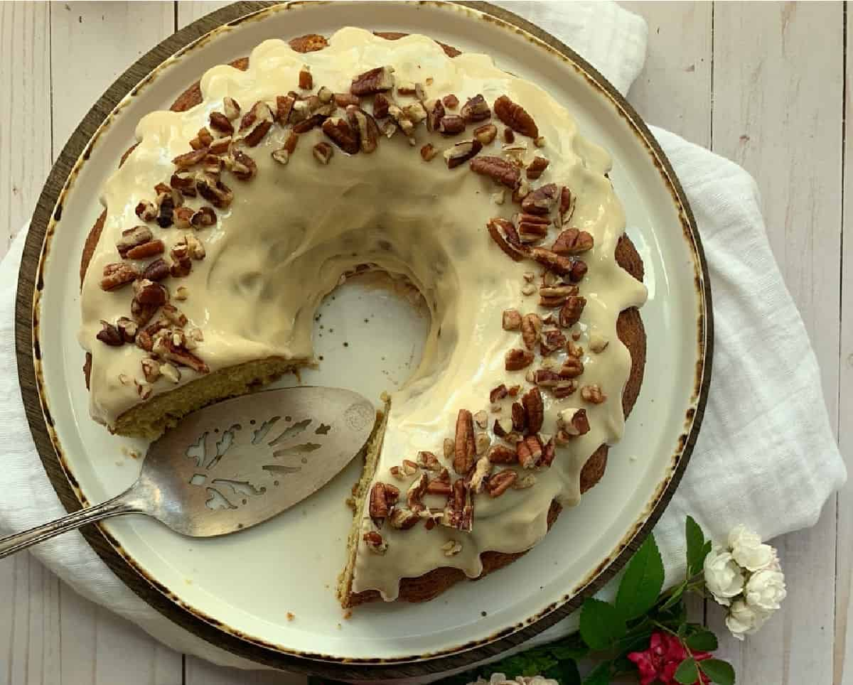 The top of a caramel glazed bundt cake the chopped pecans on top.