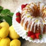 lemon bundt cake with strawberries on a cake plate.