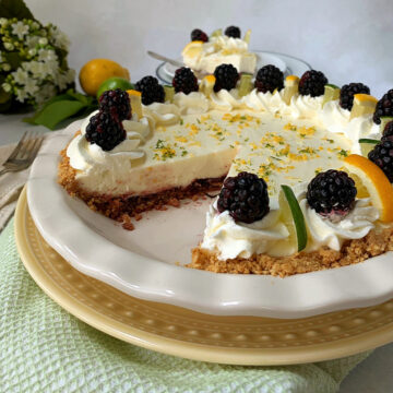 A white pie plate with a lemon lime pie with a slice cut out.