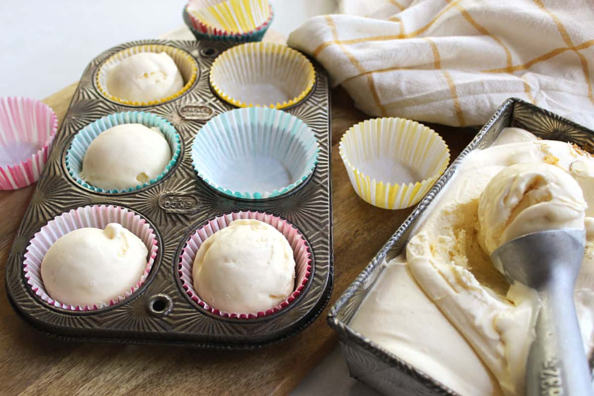 Scooping ice cream into paper liners in a muffin tin.
