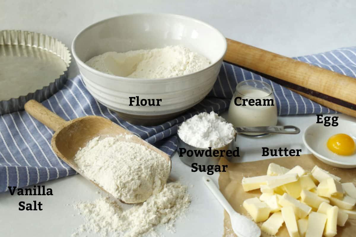 Flour, sugar, butter, egg and cream for pie dough.