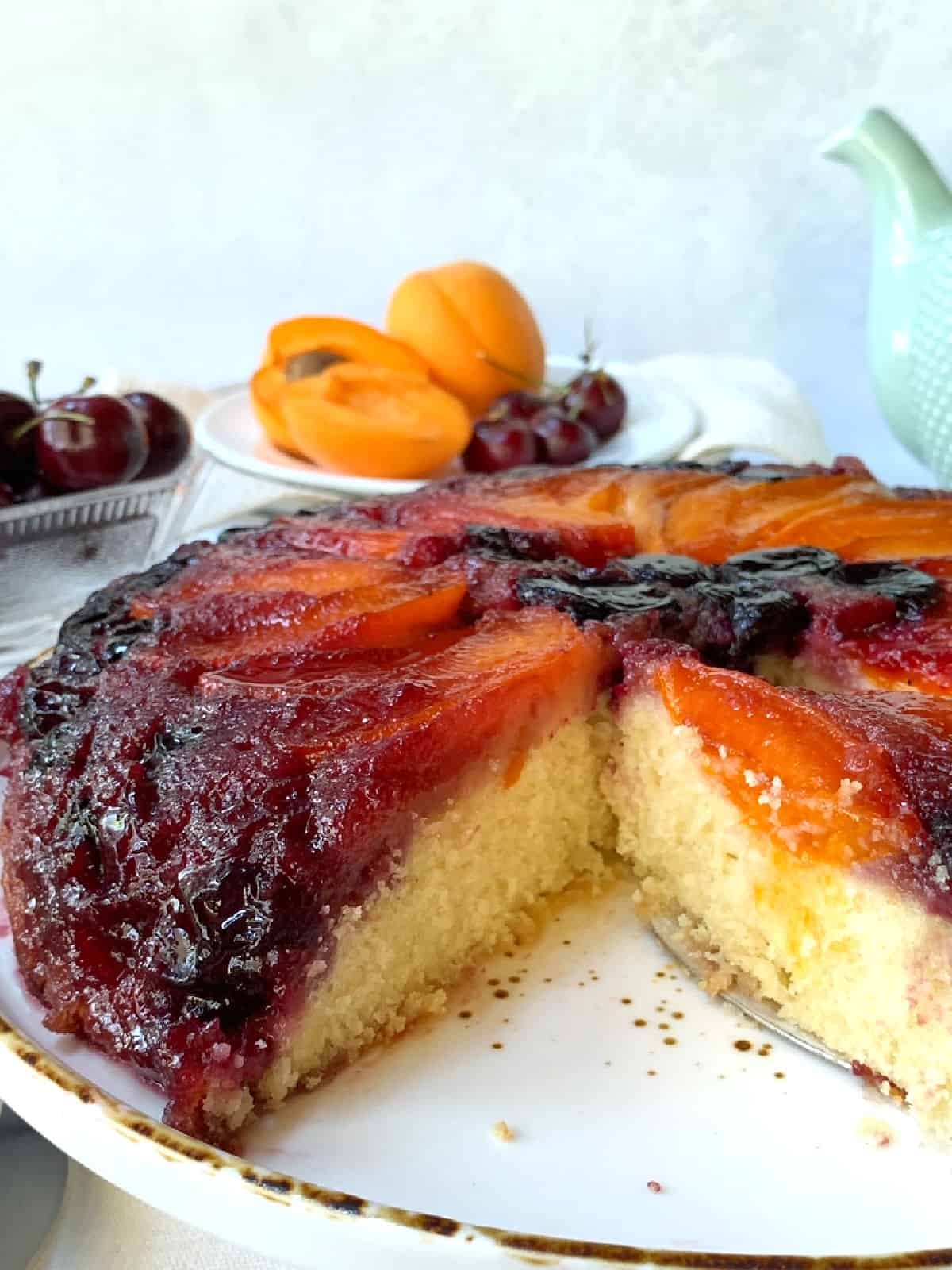 A baked apricot cherry upside down cake on a white tray.