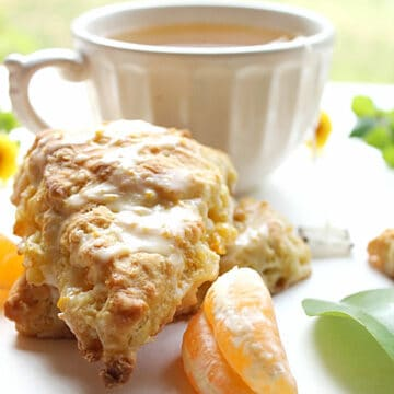 An orange scone with orange slices and a cup of tea.