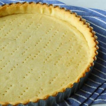 A baked tart shell on a blue towel
