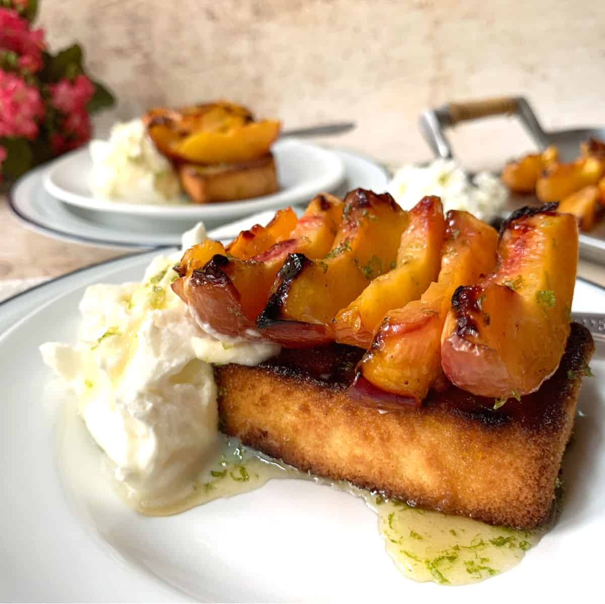 Grilled peaches on top of grilled poundcake on a white plate.