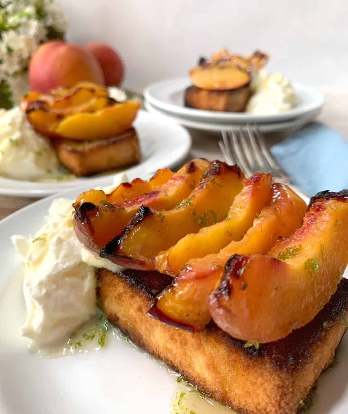 Three white plates with peaches and pound cake topped with