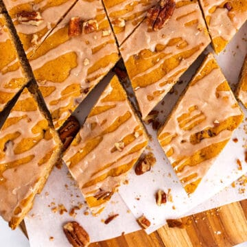 Slices of butter pecan blondies on a white piece of paper on a cutting board.