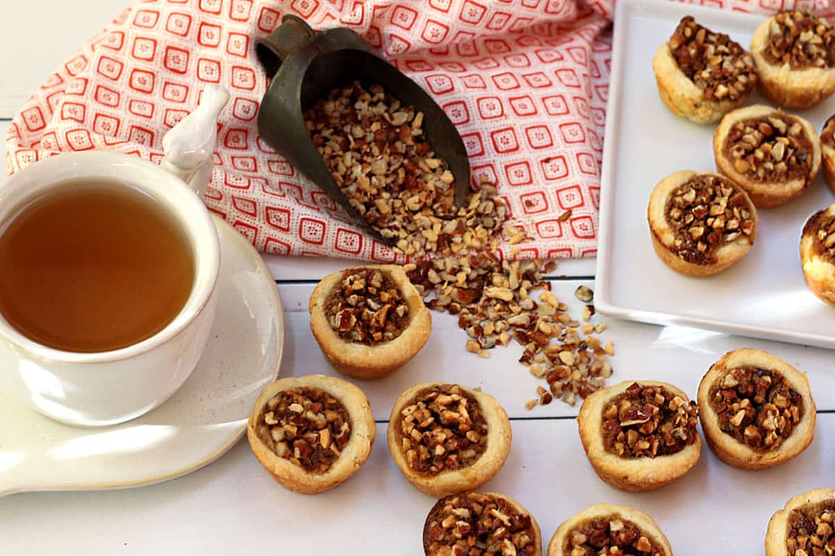 A cup of tea in a white cup with pecan tarts on a white board and a scoop of chopped peans.