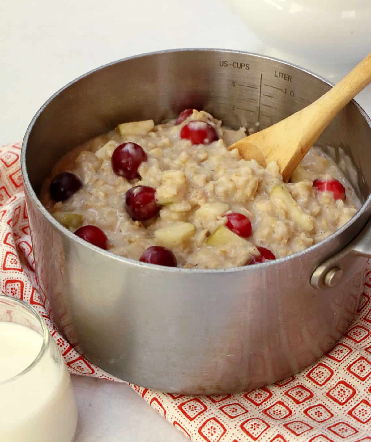 A silver pan filled with cooked oatmeal with cranberries